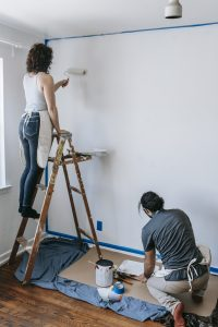 Couple painting the wall white